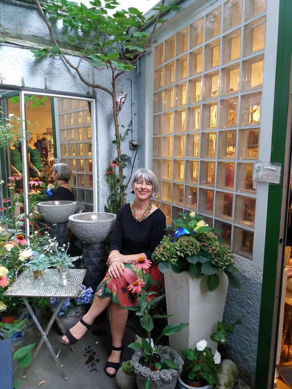 Annette Schlagheck im Damensecondhandladen München Fashion and Fantasy vor ihrem idyllischen Gartenhaus.